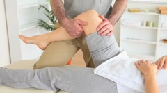 Stock Video Footage of Chiropractor stretching the knee of a woman