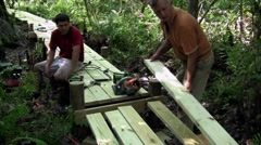 A father and son work on a wooden walkway through the Everglades. Stock Footage