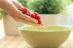 Pouring fresh fruits into a bowl, slow motion Stock Footage