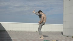 A man practices yoga on the roof. Karate kicks. - stock footage