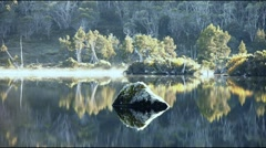 Morning mist on calm lake with rock Stock Footage