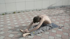 Man practices yoga on the roof. Stretching back, stretching neck. - stock footage