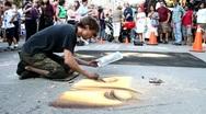 Young man drawing on street sidewalk using chalks Stock Footage