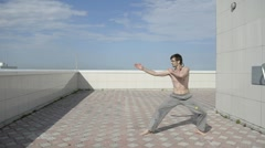 Stock Video Footage of Man practices yoga on the roof. Complex military exercises ninja.