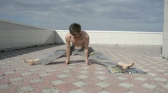 Man practices yoga on the roof. Do the splits, the emphasis on his fingers 2. Stock Footage