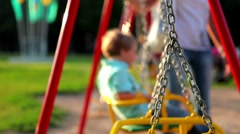 children ride on the swings at the playground - stock footage