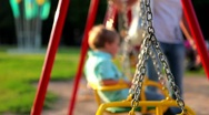 Children ride on the swings at the playground Stock Footage