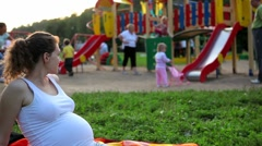 Pregnant woman looks at the children on the playground - stock footage