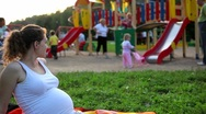 Pregnant woman looks at the children on the playground Stock Footage