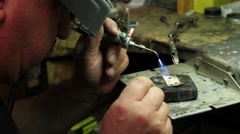 Goldsmith melting gold in his shop Stock Footage