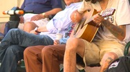 Tattooed guy sitting on bench strumming guitar Stock Footage