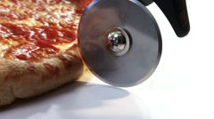 Cutting a pizza with a pizza cutter Stock Footage