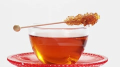 A cup of tea with a sugar swizzle stick Stock Footage