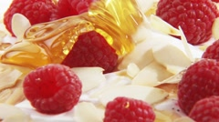 Pouring honey over cream with raspberries & flaked almonds Stock Footage