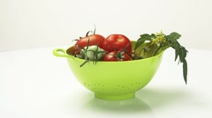 Ripe & unripe tomatoes with stem, leaves & flowers in colander Stock Footage