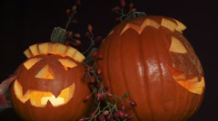 Illuminated Halloween pumpkins with autumn leaves and rose hips Stock Footage