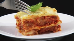 Cutting a bite-sized piece of lasagne with a fork - stock footage