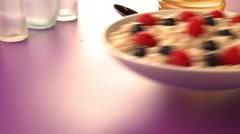 Putting a dish of porridge with berries on a table Stock Footage