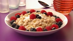 Pouring honey over porridge with berries Stock Footage
