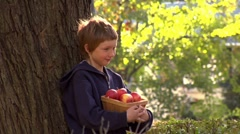 Apple falling from the head of a boy leaning against a tree Stock Footage