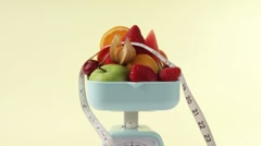 Fresh fruit and tape measure on kitchen scales Stock Footage
