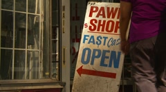 Woman walks into pawn shop, partial zoom back Stock Footage