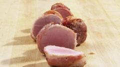 Sliced, barded pork fillet - stock footage