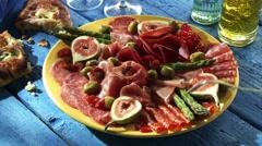 Plate of antipasti: salami, ham, figs, olives, asparagus Stock Footage
