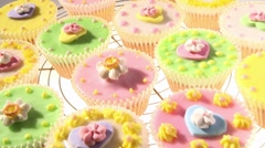 Colourful cupcakes on a cake rack - stock footage
