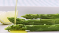 Pouring melted butter over green asparagus Stock Footage