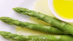 Sprinkling green asparagus with melted butter - stock footage