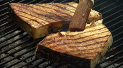 Brushing swordfish steaks on barbecue with marinade - stock footage