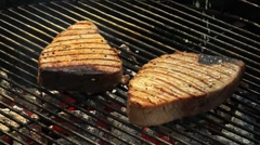 Seasoning tuna steaks on a barbecue Stock Footage