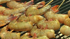 Brushing prawn skewers on a barbecue with barbecue marinade Stock Footage