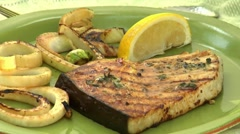 Sprinkling grilled swordfish steak with lemon juice Stock Footage