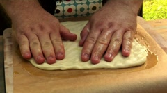 Spreading out pizza dough on baking parchment Stock Footage