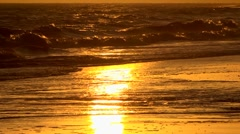 The setting sun reflected in waves as they break on the shoreline Stock Footage