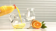 Pouring orange juice from a bottle into a jug Stock Footage
