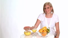 Blond woman drinking a glass of orange juice Stock Footage