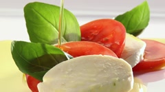Pouring olive oil over tomato and mozzarella slices Stock Footage