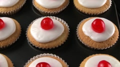 Cupcakes with cocktail cherries in muffin tin Stock Footage