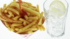 Chips with ketchup and a glass of cola with ice cubes Stock Footage