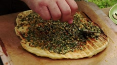 Spreading pesto on grilled flatbread Stock Footage