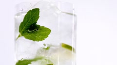 A glass of mineral water with mint leaves and slices of lime Stock Footage