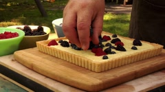 Putting fresh berries on cheese tart Stock Footage