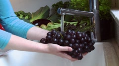 Washing red grapes under running water Stock Footage