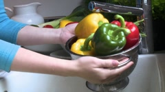 Washing peppers in a colander under running water Stock Footage