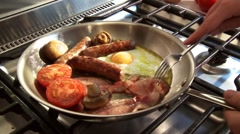 English breakfast: bacon, egg, sausage etc. in frying pan Stock Footage