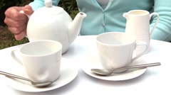 Pouring a cup of tea (outdoor shot) Stock Footage