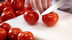 Cutting two tomatoes into quarters Stock Footage